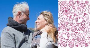 Composite image of carefree couple hugging in warm clothing. Carefree couple hugging in warm clothing against valentines pattern Royalty Free Stock Photography