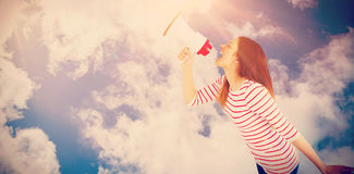 Composite image of carefree young woman making announcement with megaphone. Carefree young woman making announcement with megaphone  against bright blue sky with Royalty Free Stock Images