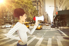 Composite image of carefree young woman shouting with megaphone. Carefree young woman shouting with megaphone  against new york street Royalty Free Stock Images