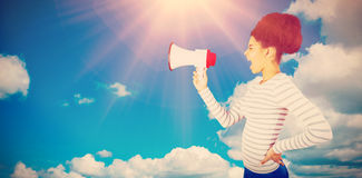 Composite image of carefree young woman shouting with megaphone. Carefree young woman shouting with megaphone  against scenic view of blue sky Royalty Free Stock Photography