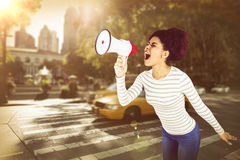 Composite image of carefree young woman yelling with megaphone Royalty Free Stock Images