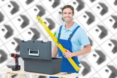 Composite image of carpenter holding spirit level at table Royalty Free Stock Photography