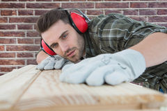 Composite image of carpenter measuring wooden plank Royalty Free Stock Photo