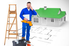 Composite image of carpenter on the phone. Carpenter on the phone  against blue house behind an architectural plan Royalty Free Stock Image
