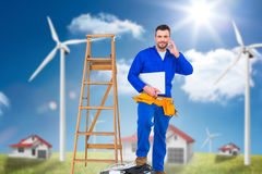 Composite image of carpenter on the phone. Carpenter on the phone  against houses in a turbine field Stock Photos