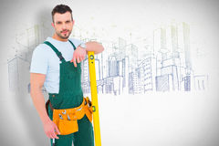 Composite image of carpenter smiling to camera with spirit level Royalty Free Stock Image