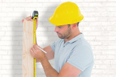 Composite image of carpenter using measure tape to mark on wooden plank Stock Image