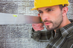 Composite image of carpenter using spirit level. Carpenter using spirit level  against grey brick wall Royalty Free Stock Photos