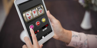 Composite image of casino slot machine game on mobile screen. Casino slot machine game on mobile screen against close-up of woman hands using digital tablet Stock Images