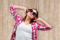 Composite image of casual brunette listening to music Royalty Free Stock Image