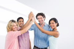 Composite image of  casual business team high fiving Royalty Free Stock Images