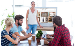 Composite image of casual businesswoman giving presentation to her colleagues Stock Image