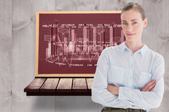Composite image of casual businesswoman looking at camera with arms crossed Royalty Free Stock Image