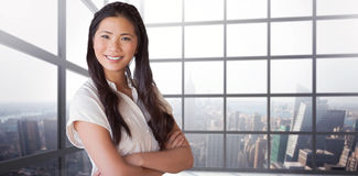 Composite image of casual businesswoman looking at camera with arms crossed Stock Photos