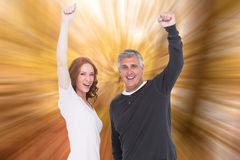 Composite image of casual couple cheering at camera Royalty Free Stock Photo