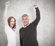 Composite image of casual couple cheering at camera. Casual couple cheering at camera against white background Stock Photo