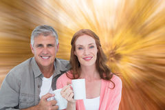 Composite image of casual couple having coffee together Royalty Free Stock Images