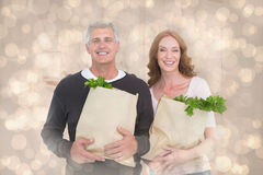 Composite image of casual couple holding grocery bags Stock Image