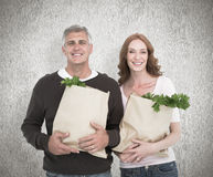 Composite image of casual couple holding grocery bags Royalty Free Stock Photography