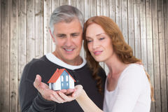 Composite image of casual couple holding small house Royalty Free Stock Image