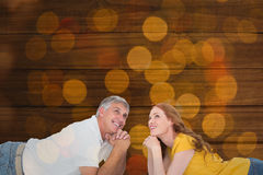 Composite image of casual couple lying on floor Stock Photos