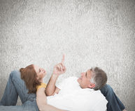 Composite image of casual couple lying on floor Stock Photography