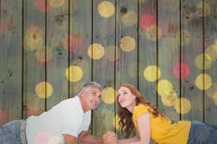 Composite image of casual couple lying and looking up Royalty Free Stock Photo