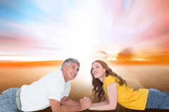 Composite image of casual couple lying and looking up Royalty Free Stock Image