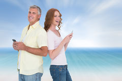 Composite image of casual couple sending text messages Stock Image