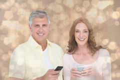 Composite image of casual couple sending text messages Royalty Free Stock Photography