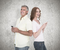 Composite image of casual couple sending text messages Royalty Free Stock Photo