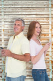 Composite image of casual couple sending text messages Royalty Free Stock Photos