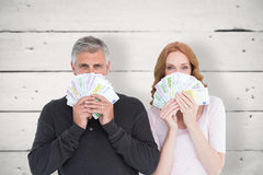 Composite image of casual couple showing their cash Royalty Free Stock Images