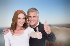 Composite image of casual couple showing thumbs up Royalty Free Stock Image