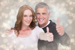 Composite image of casual couple showing thumbs up Royalty Free Stock Photo