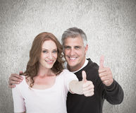 Composite image of casual couple showing thumbs up Royalty Free Stock Images