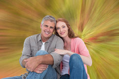 Composite image of casual couple sitting and smiling Stock Image