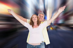 Composite image of casual couple smiling with arms raised Royalty Free Stock Photo