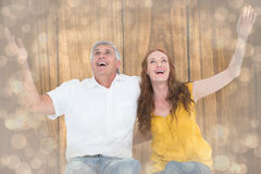 Composite image of casual couple smiling with arms raised Stock Photos