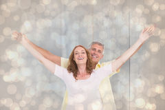 Composite image of casual couple smiling with arms raised Stock Photo