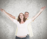 Composite image of casual couple smiling with arms raised Royalty Free Stock Photography