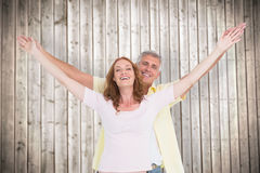 Composite image of casual couple smiling with arms raised Stock Photography