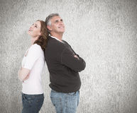 Composite image of casual couple smiling and looking up Stock Image