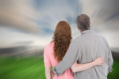 Composite image of casual couple standing arm around Royalty Free Stock Image