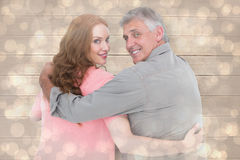Composite image of casual couple standing arms around Royalty Free Stock Image