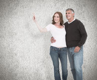 Composite image of casual couple walking and pointing Stock Images