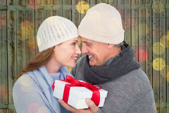 Composite image of casual couple in warm clothing holding gift Stock Photography