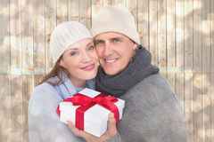 Composite image of casual couple in warm clothing holding gift Royalty Free Stock Image