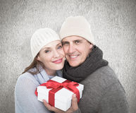 Composite image of casual couple in warm clothing holding gift Royalty Free Stock Photography