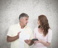 Composite image of casual couples working out their bills Royalty Free Stock Image